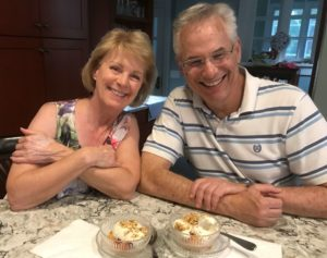 Woman and man smiling with peaches and ice cream snack.