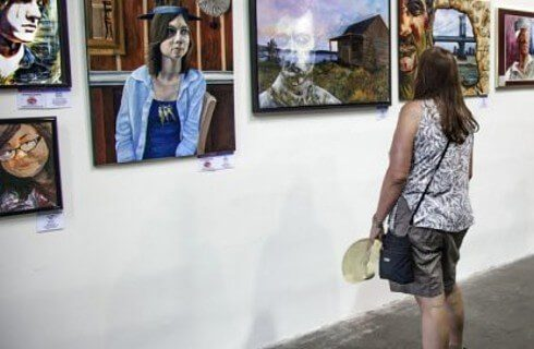 A woman in shorts and a tank top looking at a wall full of hanging artwork