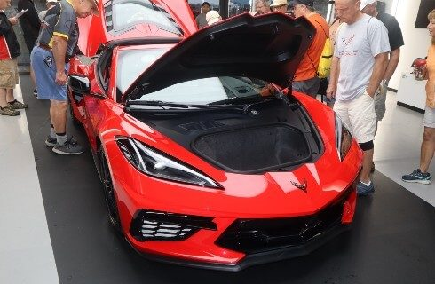 Shiny red sports car with hood and rear hatch open and people looking inside