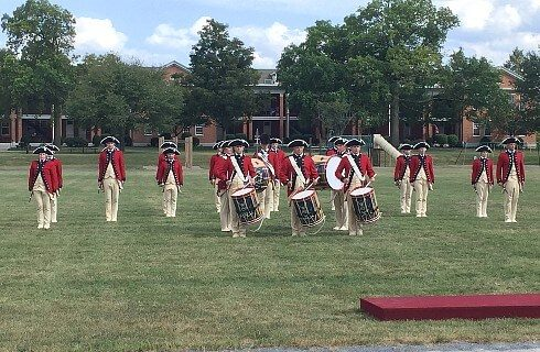 A group of people in Revolutionary War attire, holding instruments and walking across a lawn