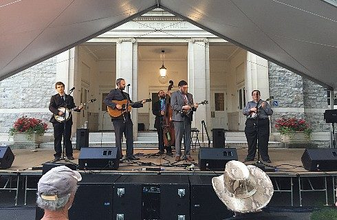 A group of five men placing various instruments on an outdoor stage under a large awning