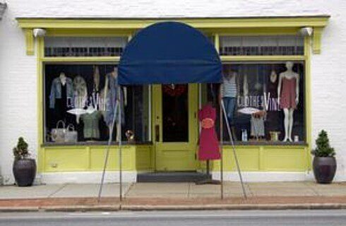 Outside view of a storefront with a blue awning, green trim and clothing displays in the windows