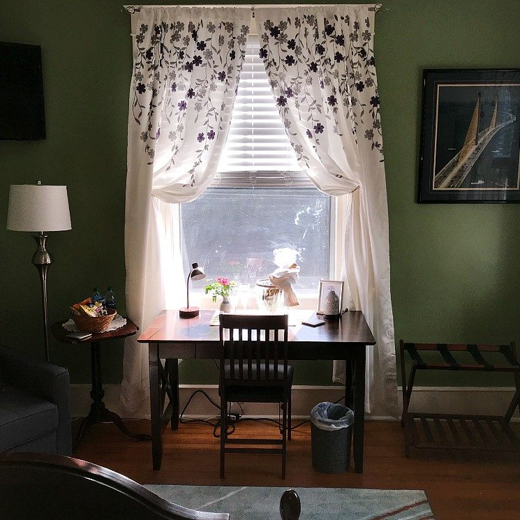Guest room with writing desk in front of a large window, sitting chair with side table and lamp