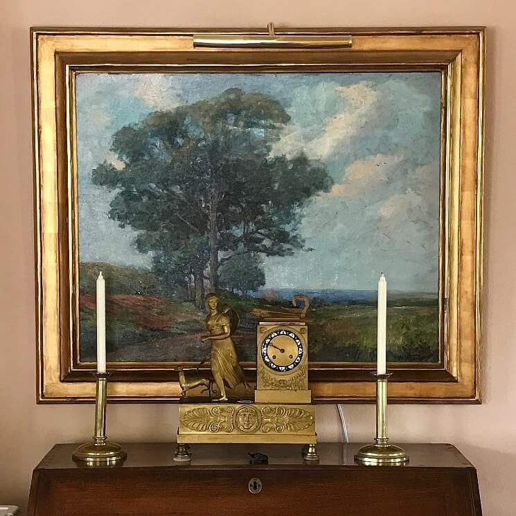Painting of a landscape in a gold frame hanging over an antique desk with candlesticks and gold statue