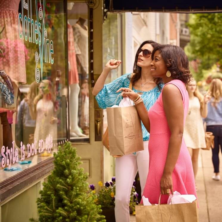 Two ladies holding brown paper shopping bags standing outside in front of a store front window