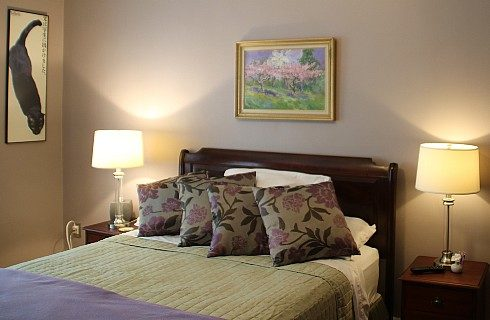 Bright guest room with queen bed in green and purple linens and two side tables with lamps