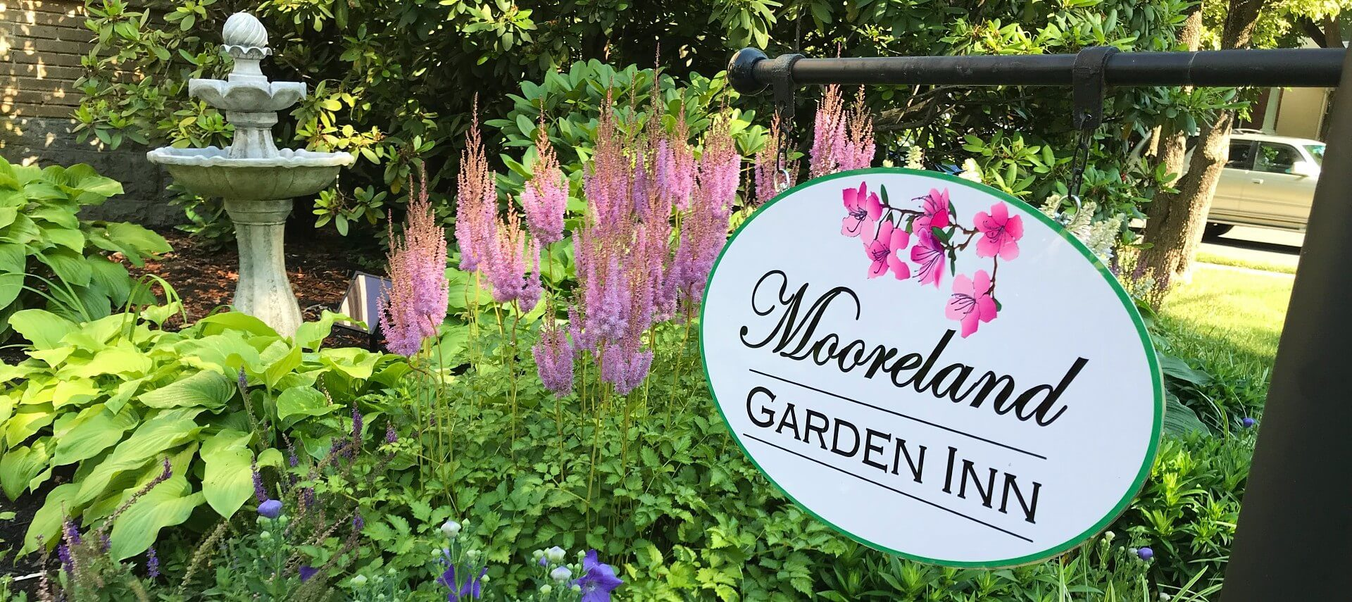 Large white oval business sign with black text hanging over a garden bed of pink and purple flowers and water fountain