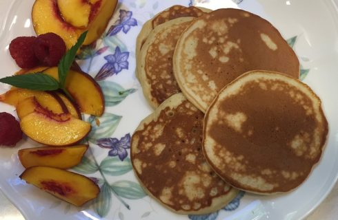 Flowered plate with five golden pancakes, sliced nectarines and raspberries