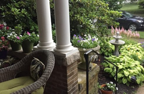 Corner of a front porch with brick wall, white columns, wicker chair and lush garden beds