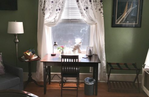 Brown writing desk in front of a large window with white floral curtains in a green guest room