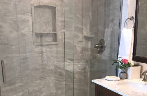 Large stand up shower with glass doors next to single vanity with marble countertop and large framed mirror
