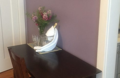 Dark brown desk with a vase of flowers and champagne bottle with a glass against a purple wall