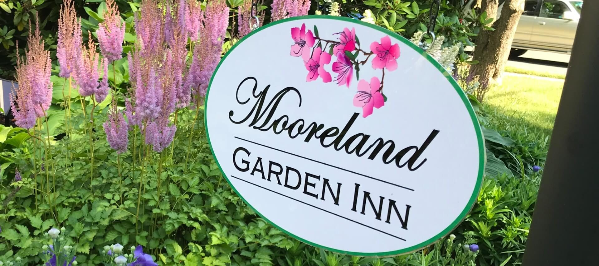 Large white oval business sign with black text and pink flowers hanging over a flower bed