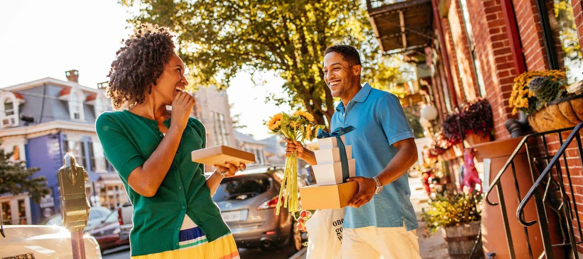 A man and woman smiling and looking at each other while holding packages standing outside on a downtown street