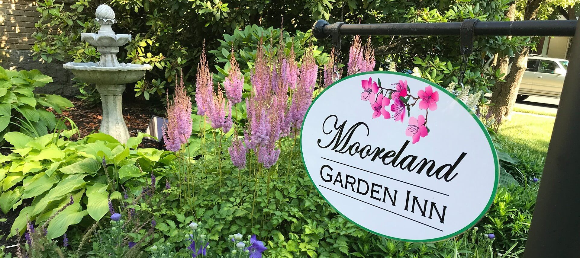 White oval business sign hanging on a black frame over a lush garden bed of flowers and water fountain